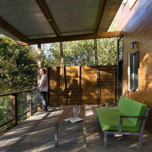 Example of a trendy deck design in Dallas with a roof extension
