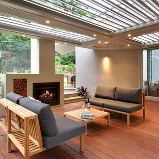 Mid-sized contemporary backyard deck in Sydney with a fire feature and a roof extension.