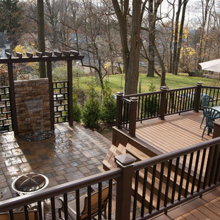 Example of a mid-sized trendy backyard water fountain deck design in New York with a pergola