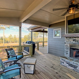 Mid-sized mountain style backyard deck photo in Atlanta with a fireplace and a roof extension