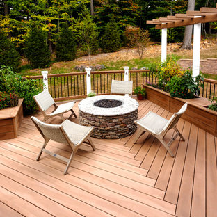 Example of a large transitional backyard deck design in New York with no cover and a fire pit