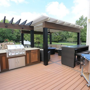 Large contemporary back terrace in St Louis with a pergola.