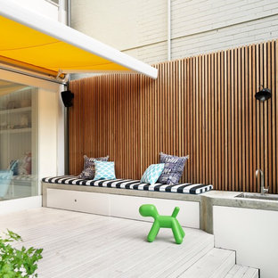 Example of a mid-sized trendy backyard outdoor kitchen deck design in Sydney with an awning