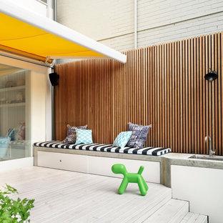 Esempio di una terrazza design di medie dimensioni e dietro casa con un parasole
