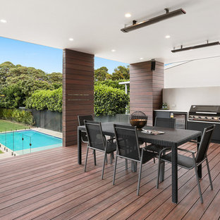Design ideas for a mid-sized contemporary backyard deck in Sydney with an outdoor kitchen and a roof extension.