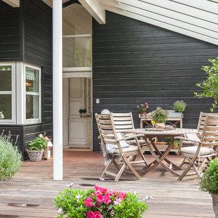 Esempio di una grande terrazza nordica dietro casa con un giardino in vaso e una pergola