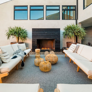 Huge trendy side yard deck photo in Los Angeles with a fire pit and no cover