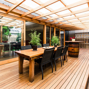 This is an example of a contemporary backyard deck in Geelong with a pergola.