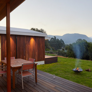Inspiration for a contemporary backyard deck in Wollongong with a fire feature and a roof extension.
