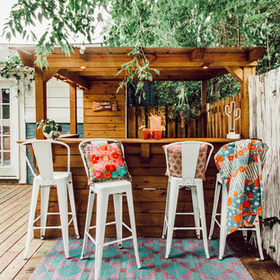 Eclectic backyard deck photo in Nashville with a pergola