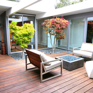 Example of a mid-sized 1960s courtyard deck design in San Francisco with no cover