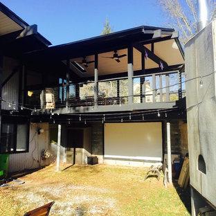 Ispirazione per una grande terrazza minimalista dietro casa con un tetto a sbalzo