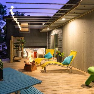 Ispirazione per terrazze e balconi moderni di medie dimensioni e dietro casa con un focolare e un tetto a sbalzo