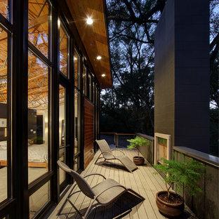 Immagine di una terrazza design di medie dimensioni e nel cortile laterale con un focolare e un tetto a sbalzo