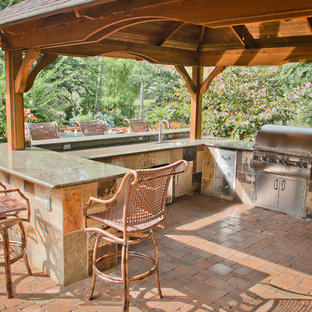 This is an example of a large mediterranean back terrace and balcony in Houston with an outdoor kitchen and a pergola.