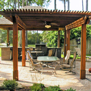 Large mediterranean back terrace and balcony in Houston with an outdoor kitchen and a pergola.
