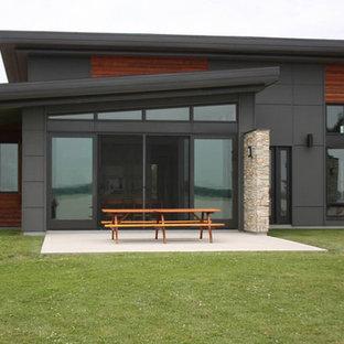 Ispirazione per una terrazza moderna di medie dimensioni e dietro casa con fontane e un tetto a sbalzo