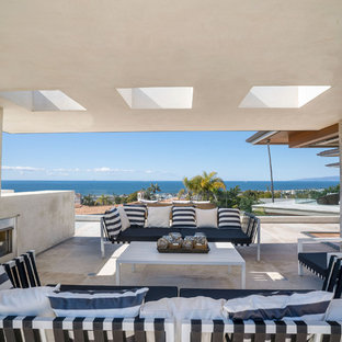 Large beach style rooftop rooftop deck photo in Los Angeles with a fireplace and a roof extension