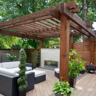 Esempio di una terrazza minimalista di medie dimensioni e dietro casa con un focolare e una pergola