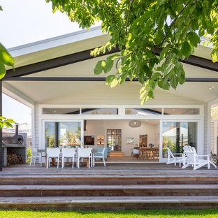 Deck - large transitional backyard deck idea in Auckland with a fireplace and a roof extension