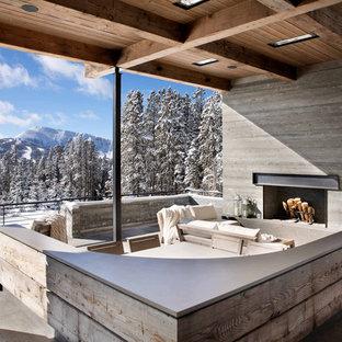 Modelo de terraza rústica, en anexo de casas, con chimenea