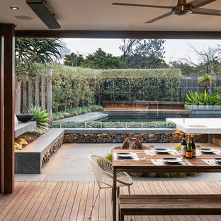 Design ideas for a contemporary backyard deck in Melbourne with a fire feature and a roof extension.