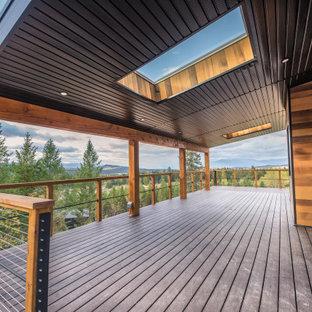 Aménagement d'une très grande terrasse et balcon arrière industrielle avec une extension de toiture.
