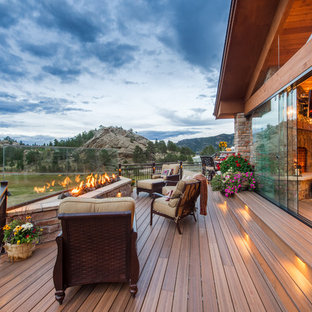Example of a large mountain style backyard deck design in Denver with a roof extension and a fire pit