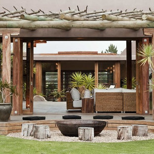 Example of a large trendy courtyard deck design in Other with a pergola