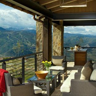 Inspiration pour une terrasse arrière chalet de taille moyenne avec une extension de toiture.