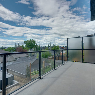 Example of a transitional backyard privacy deck design in Calgary with an awning