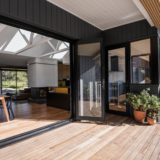 This is an example of a large retro back terrace and balcony in Other with a roof extension.