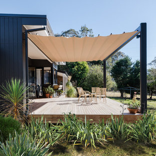 This is an example of a large midcentury backyard deck in Wollongong with an awning.