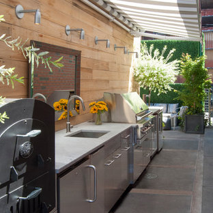 Design ideas for a large contemporary roof terrace and balcony in New York with an outdoor kitchen and an awning.