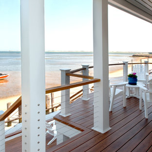 Example of a beach style backyard deck design in Boston with a roof extension