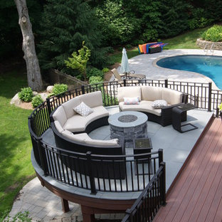 Example of a huge arts and crafts backyard deck design in New York with a fire pit