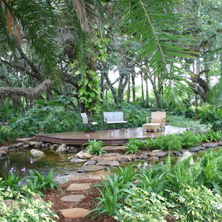 Example of an island style backyard water fountain deck design in Tampa with no cover