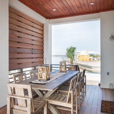Large beach style side yard deck photo in Other with a roof extension