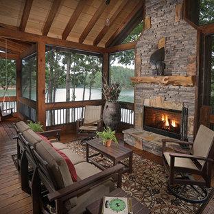 Ejemplo de terraza rústica, en patio lateral y anexo de casas, con chimenea