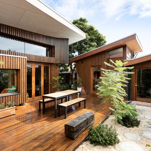 Photo of a mid-sized contemporary backyard deck in Melbourne with a roof extension.