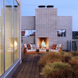 Foto di una grande terrazza moderna sul tetto con un focolare e nessuna copertura