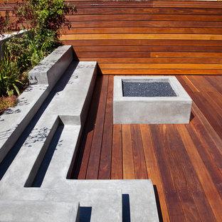Foto på en stor funkis terrass på baksidan av huset, med en öppen spis