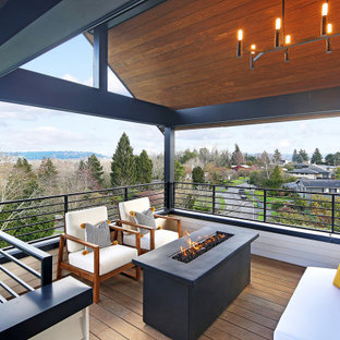 Photo of a mid-sized scandinavian deck in Seattle with a fire feature and a roof extension.