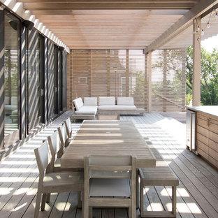 Foto de terraza nórdica con cocina exterior y pérgola
