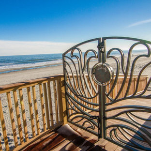 Large beach style backyard metal railing deck skirting photo in Charleston