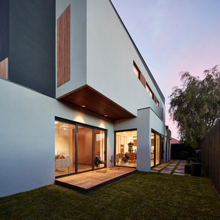 This is an example of a modern side yard deck in Melbourne with a roof extension.