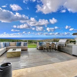 Idee per una grande terrazza costiera dietro casa con un focolare e nessuna copertura