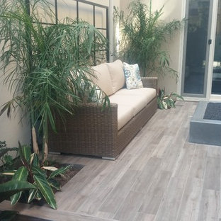 Small trendy courtyard deck photo in Orange County with a fire pit