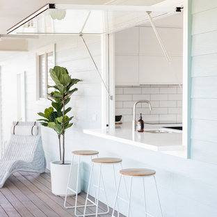 Inspiration for a beach style backyard deck in Sunshine Coast with a roof extension.