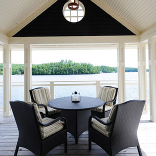 Inspiration for a mid-sized beach style backyard deck remodel in Other with a roof extension